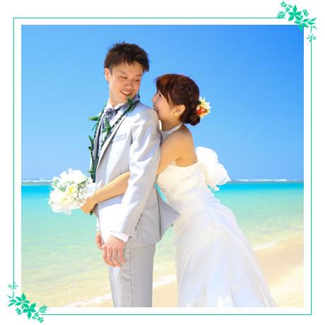 ハワイのビーチでウエディングドレスを着て記念撮影